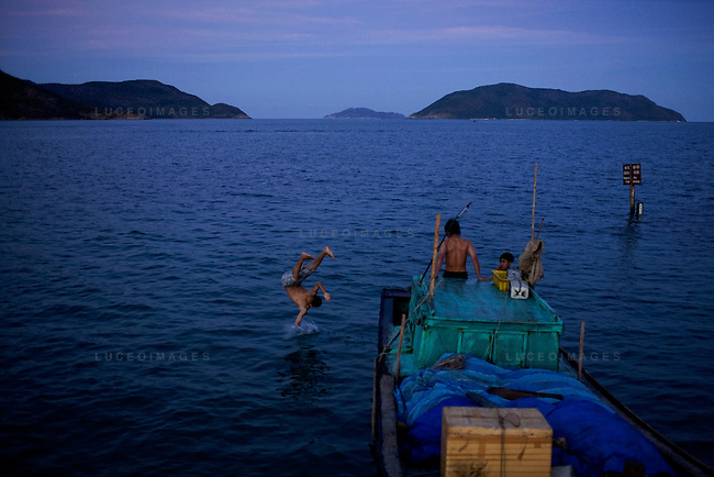 Children jump off a boat docked at Pier 914 on Con Son Island, part of Con Dao Islands in Vietnam. The pier is named after the number of prisoners who were killed during the construction process. Photo taken Thursday, May 5, 2010...Kevin German / LUCEO For the New York Times