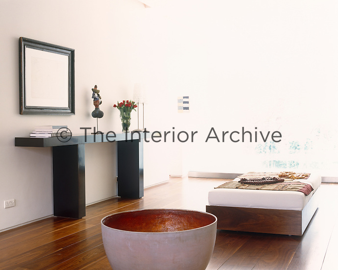 In the entrance hall to a Dublin house a small painting by Sean Scully is highlighted against bright white walls  and an outsize ceramic bowl has been placed next to an ottoman