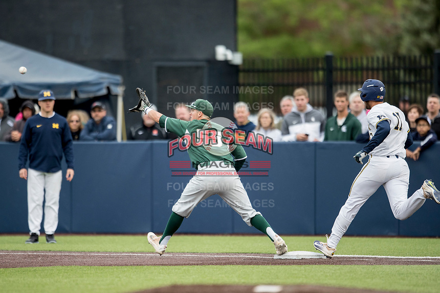 Michigan State Spartans first baseman Zach McGuire (55) stretches for a throw as Michigan Wolverines baserunner Drew Lugbauer (17) arrives at first on May 19, 2017 at Ray Fisher Stadium in Ann Arbor, Michigan. Michigan defeated Michigan State 11-6. (Andrew Woolley/Four Seam Images)