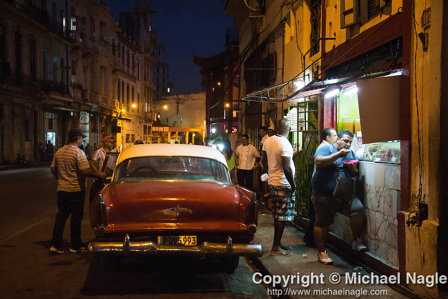HAVANA, CUBA -- MARCH 23, 2015:  People walk on the street at dusk in Havana, Cuba on March 23, 2015. Photograph by Michael Nagle