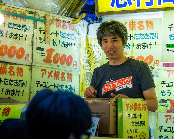 A vendor working in one of the food tents in a market near the Ueno station