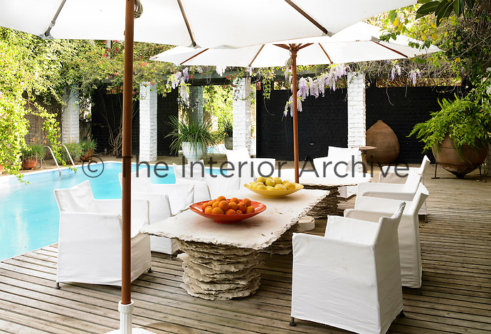 Near an outdoor pool, two tables with legs composed of layers of hand-chiseled Jerusalem stone are used for casual dining with seating being provided by white cloth covered chairs and parasols for shade.