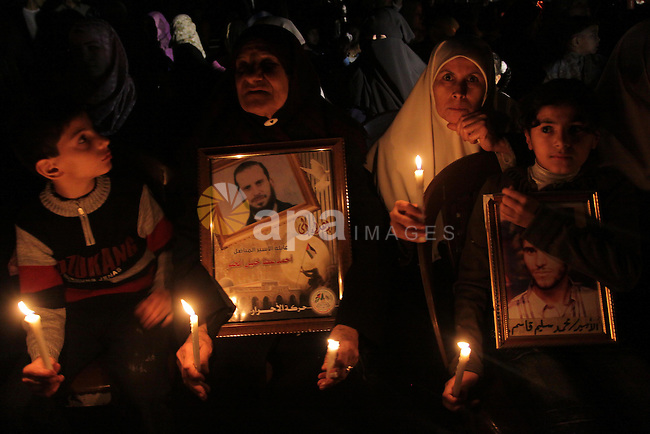 """Palestinian women and children stage a candlelight protest against the continuing Israeli blockade of the Gaza Strip on April 5, 2010 in Gaza City. Israel imposed strict closures on Gaza's borders after Israeli soldier Gilad Shalit was captured by Palestinian militants and tightened them when Hamas seized power in June 2007, sealing the territory of 1.5 million people off from all but vital humanitarian aid. Arabic writing on placard reads: """"Freedom for Gaza."""" Photo by Mohammed Asad"""