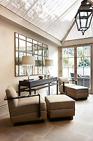 A pair of armchairs with matching footstools flank a sidetable in this conservatory sitting-room