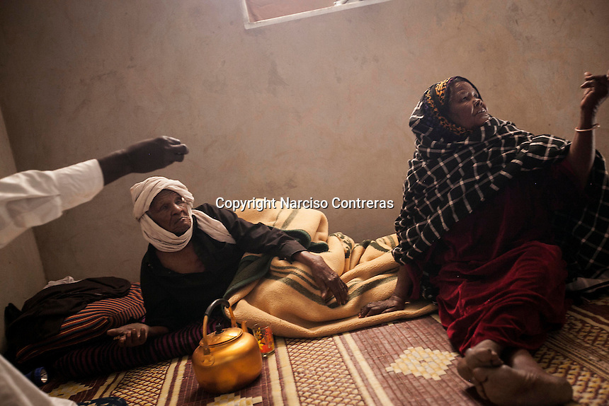 November 22, 2014 - Murzuq City, Libya: A Tebu elder couple displaced from Ubari battleground are seen inside a temporary shelter outskirst Murzuq. The woman was wounded by shrapnel in her arm during a mortar attack. Fighting around Southwest Ubari region ignited after Tuareg militias from Mali and Libya sized control over the vast oilfield installations aligned with the Third Force of Misrata armed forces. Since then raged battles have taken place between two factions: one faction of Tuareg fighters lead by Third Force from Misrata pushing to clean the region from the other faction of Tebu tribal fighters defending their controlled territory. (Photo/Narciso Contreras)