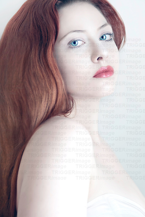 Close up of young woman with pale skin and long red hair looking over shoulder at camera