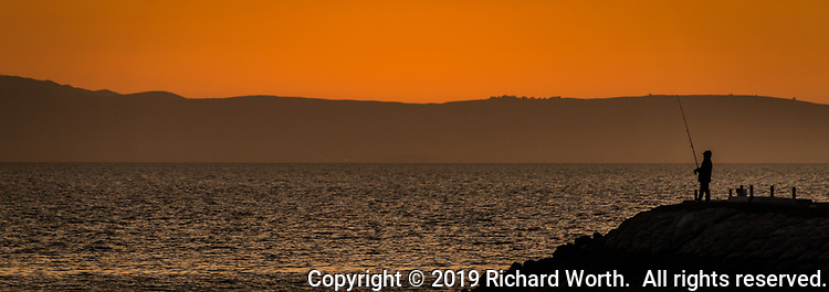 Under sunset's glowing sky, a fisherman in silhouette along San Francisco Bay with the Santa Cruze Mountains at the horizon.
