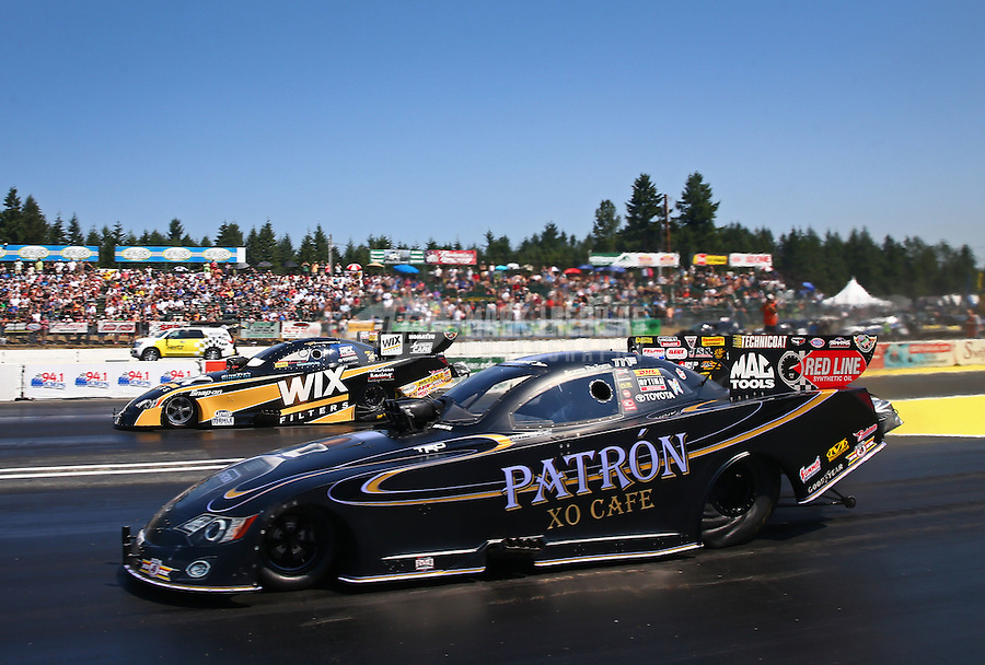 Aug. 3, 2014; Kent, WA, USA; NHRA funny car driver Alexis DeJoria (near) races alongside Tony Pedregon during the Northwest Nationals at Pacific Raceways. Mandatory Credit: Mark J. Rebilas-USA TODAY Sports