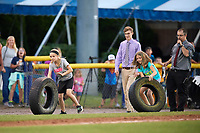 Two young fans participate in an on field promotion, the dizzy bat tire race, during a Batavia Muckdogs game against the Auburn Doubledays on June 19, 2017 at Dwyer Stadium in Batavia, New York.  Batavia defeated Auburn 8-2 in both teams opening game of the season.  (Mike Janes/Four Seam Images)