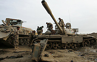 Iraqi mechanics from the 1st company, 1st armour battalion of the 1st mechanized Iraqi Army Brigade repair the transmission of a T 55 tank  while conducting  patrols, check points and observation posts on code name route Michigan, the main road of Ramadi in the week during the national election on TUE Dec 13 2005 in Ramadi, Iraq. 1st company is part of the first armor battalion of the New Iraqi Army. it has started its training in January 2005. after 50 days their 35 russian and chinese built T 55 tanks begun conducting operations under the guidance of a US military adivisor team. in April 2005 they patrolled in the Abu Ghraib area concluding their first significant mission. While these old tanks are rolling on the ramadi streets more modern T72s are getting ready to become fully operational in Taji, their main base. the Iraqi army wanted to show their power in ramadi during the Dec 15 elections displaying their new armour company. but like all the other Iraqi forces they are not going to secure the polling sites, staying in the rear with the rest of the iraqi and coalition forces. T 55s are very old tanks. production begun in the late 50s to the late 70s. athough obsolete many countries still use the T55 as their main heavy armoured combat vehicle. slow, heavvy and with very little room for the crew it suffers from many mechanical problems constantly challenging the iraqi mechanics and engineers.
