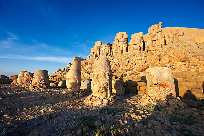 Pictures & Images of the statues of around the tomb of Commagene King Antochus 1 on the top of Mount Nemrut, Turkey. Stock photos & Photo art prints. In 62 BC, King Antiochus I Theos of Commagene built on the mountain top a tomb-sanctuary flanked by huge statues (8–9 m/26–30 ft high) of himself, two lions, two eagles and various Greek, Armenian, and Iranian gods. The photos show the broken statues on the  2,134m (7,001ft)  mountain. 4