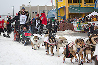 Allen Moore and team leave the ceremonial start line at 4th Avenue and D street in downtown Anchorage during the 2013 Iditarod race. Photo by Jim R. Kohl/IditarodPhotos.com