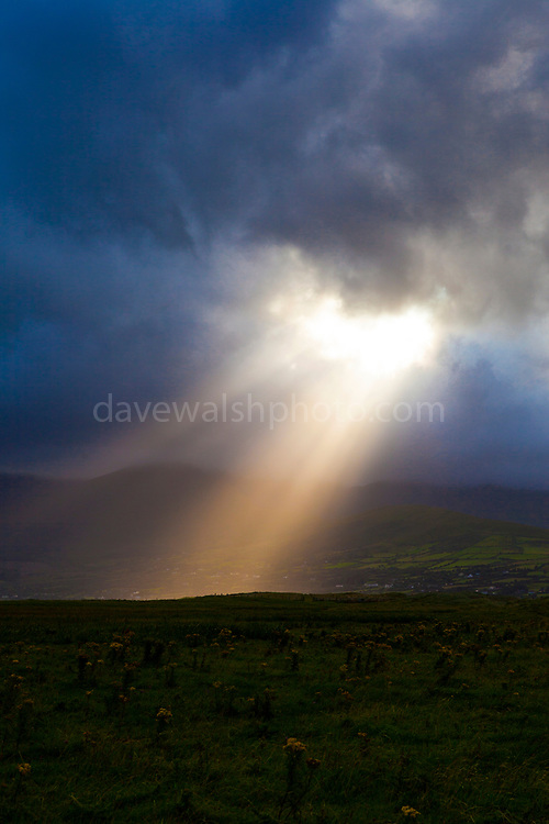 Sunlight breaks through the clouds above Mounta Brandon, near Cloghane. Photo made on Fermoyle Beach, on the Dingle Peninsula, Ireland,