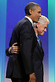US President Barack Obama (front) is greeted by former US President Bill Clinton (back) at the Clinton Global Initiative (CGI) in New York, New York, USA, 23 September 2010. President Obama joined sixty-four current and former heads of state in attending the sixth annual meeting of the CGI.  The commitment of CGI members has improved the lives of more than 220 million people in 170 countries, according to President Bill Clinton.  The 2010 meeting features a session on 'Peace and Beyond in the Middle East'.  .Credit: Michael Reynolds - Pool via CNP