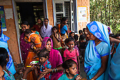 Caretakers and family workers gather to have their children checked during a mass screening at the local health centre in Hanuman Nagar, Saptari, Nepal.