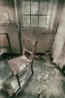 Pale pink hard chair by window, derelict West Park Asylum, Epsom, Surrey, processed to emulate wet plate technique.
