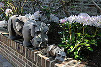 A bleached wooden sculpture of a hippo and baby adorns the brick wall that lines one of the raised flowerbeds in the courtyard garden