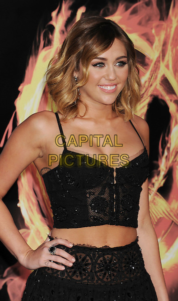 "Miley Cyrus.The World Premiere of ""The Hunger Games"" at Nokia Theatre in Los Angeles, California at LA Live, USA..March 12th, 2012.half length black lace sheer skirt top belly stomach midriff cleavage hand on hip .CAP/ROT/TM.©Tony Michaels/Roth Stock/Capital Pictures"