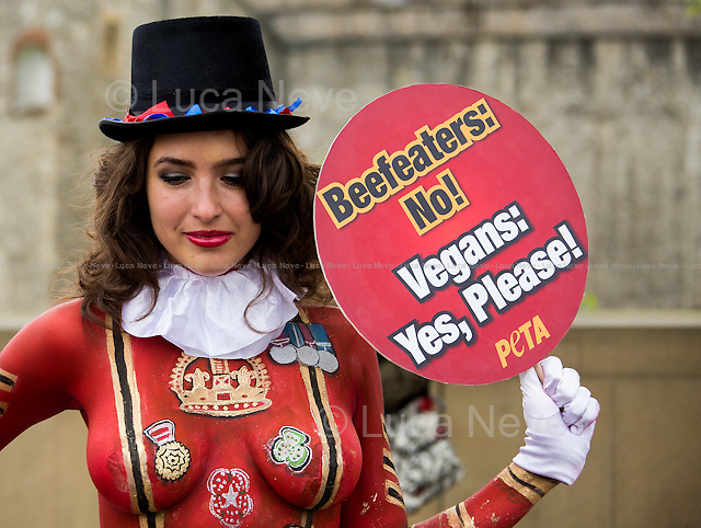"London, 22/04/2014. Today, two PETA (People for the Ethical Treatment of Animals) models stood outside the Tower of London showing placards with the words ""Beefeaters: No! Vegans: Yes, Please!"". The aim of the demonstration, held the day before St George's Day, was to urge English people to ""kick their meat-eating habit for their health, the environment, animals and England"" and became vegans."