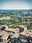 Farms and fields beyond the hilltop village of  San Gimignano, Siena-Tuscano, Italy
