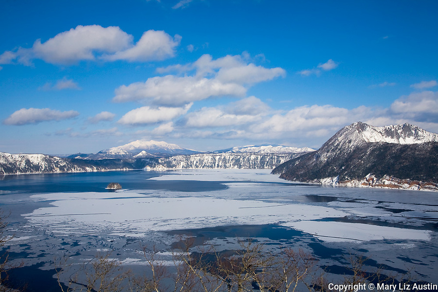 Akan National Park, Hokkaido Island, Japan<br /> Frozen Lake Mashu, a volcanic crater lake with Mount Shari in the distance