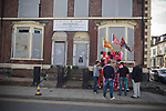 Supporters buying souvenirs from a stall outside boarded up and derelict houses in a street adjacent to Anfield, home of Liverpool football club, pictured before the club took on Fulham in a Premier League match during the 2009-10 season. The club was one of the most successful and best supported teams in England and which won many domestic and European trophies. The most-famous part of the stadium was the Kop, where the Liverpool fans sat during games. Photo by Colin McPherson