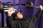 Education High School physical education elective weight lifting teenager in baseball cap using equipment