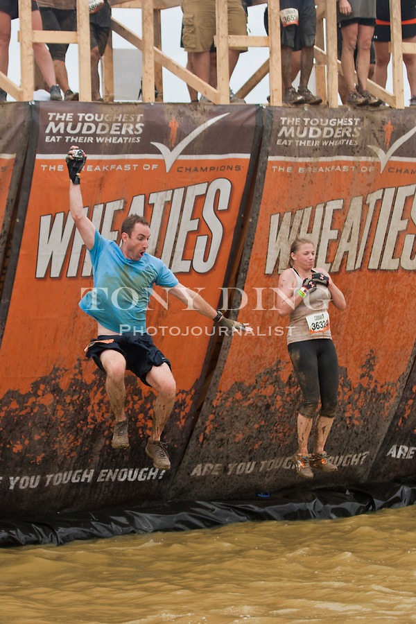 "16 April 2010: Competitors jumps off and climbs out of the ""Walk the Plank"", one of twenty obstacles in the Tough Mudder adventure endurance race at Michigan International Speedway in Brooklyn, Michigan."