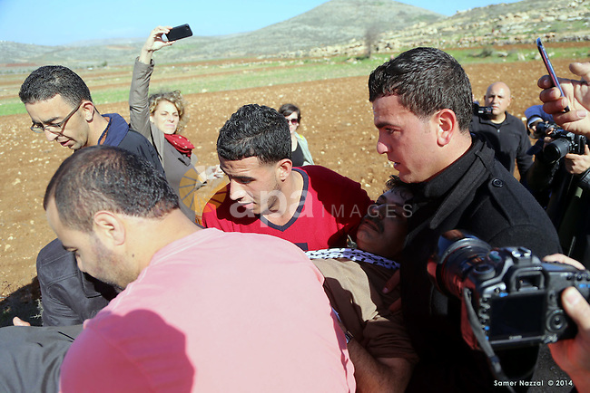 Palestinian protesters treat Palestinian official Ziad Abu Ein, in charge of the issue of Israeli settlements for the Palestinian Authority, as he lays on the ground after being beaten by Israeli soldiers, during a demonstration in the village of Turmus Aya near Ramallah, on December 10, 2014. Abu Ein died after being beaten by Israeli forces during a protest march in the West Bank, medical and security sources said. Photo by Shadi Hatem