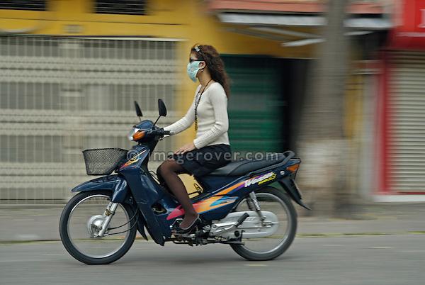 Asia, Vietnam, Hanoi. Hanoi old quarter. Girl with face mask on motorbike rushing through Hanoi.