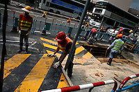 A construction crew works to repair a road in the Kowloon district of Hong Kong.