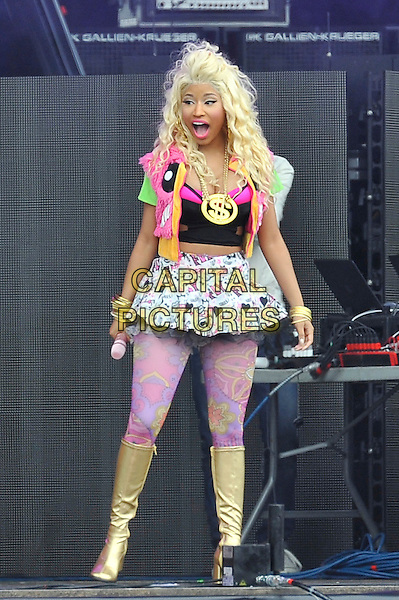 Nicki Minaj.performing at the Barclaycard Wireless Festival, Hyde Park, London, England. 7th July 2012..music live gig on stage show full length live on stage pink tights gold dollar sign necklace  gold knee high boots print patterned white mini skirt  black crop bra top  fur jacket gilet mouth open funny tulle microphone .CAP/MAR.© Martin Harris/Capital Pictures.