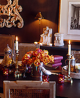 Close-up of the dining room table with silver candlesticks, birds and a vase filled with fresh tulips