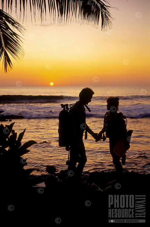 Couple with scuba gear standing at the shoreline are silhouetted against a golden sunset.