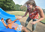 Three-year old Youel, a resettled refugee from Eritrea, slides toward Erin Chesson, an employment specialist with Church World Service, in a playground in Durham, North Carolina. <br /> <br /> The boy and his mother were resettled in Durham by Church World Service, which resettles refugees in North Carolina and throughout the United States.<br /> <br /> <br /> Photo by Paul Jeffrey for Church World Service.
