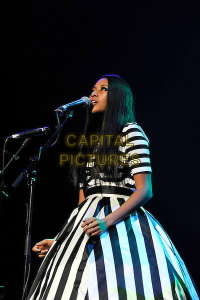 VV BROWN (VANESSA BROWN).Performs live during the 'Women Of The World: Equals' live concert to celebrate the 100th anniversary of International Women's Day, Royal Festival Hall, London, England, UK, March 11th 2011..half length concert music gig live on stage black and white striped dress side microphone singing hand .CAP/MAR.© Martin Harris/Capital Pictures.