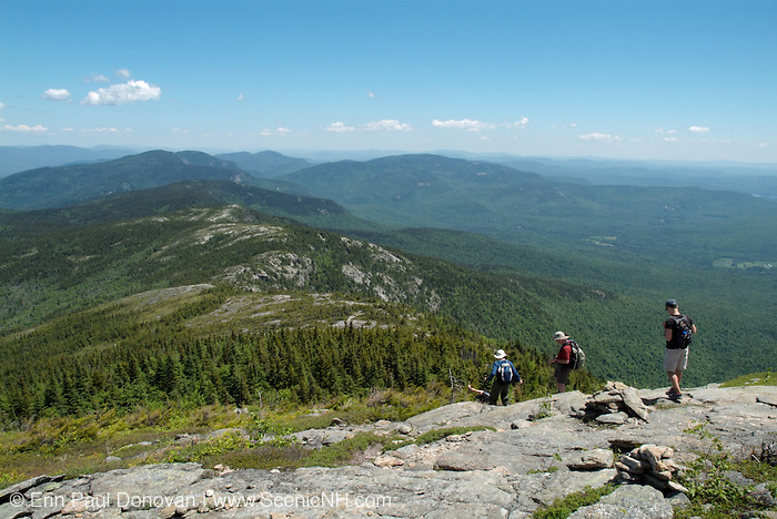Three hikers descend North Baldface Mountain using Baldface Circle Trail in the White Mountains, New Hampshire USA during the spring months.