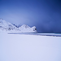 Snow covered beach and winter storm, Unstad, Lofoten islands, Norway