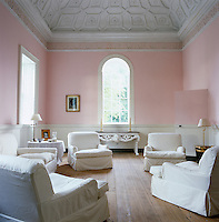 A contemporary style of comfortable seating in white loose covers has been struck in this neoclassical drawing room with pale pink walls and coffered ceiling