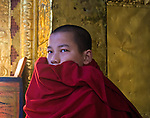 A young monk, wrapped in his dark red robe covering his mouth, sits in a quiet place surrounded by golden walls in the Wangdue Phodrang Dzong high in the hills of Bhutan.