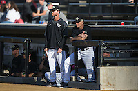 Wake Forest Demon Deacons assistant coach Matt Hobbs (left) and head coach Tom Walter (right) watch from the dugout during the game against the Florida State Seminoles at David F. Couch Ballpark on April 16, 2016 in Winston-Salem, North Carolina.  The Seminoles defeated the Demon Deacons 13-8.  (Brian Westerholt/Four Seam Images)