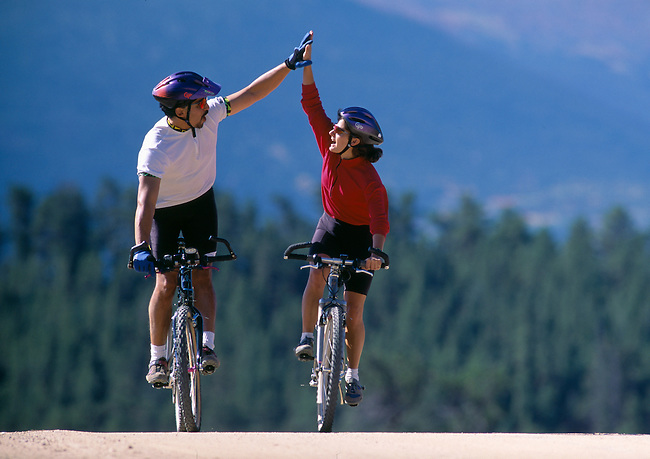 """We did it!"" as a young couple finishes biking up a hill, Rocky Mtns, CO"