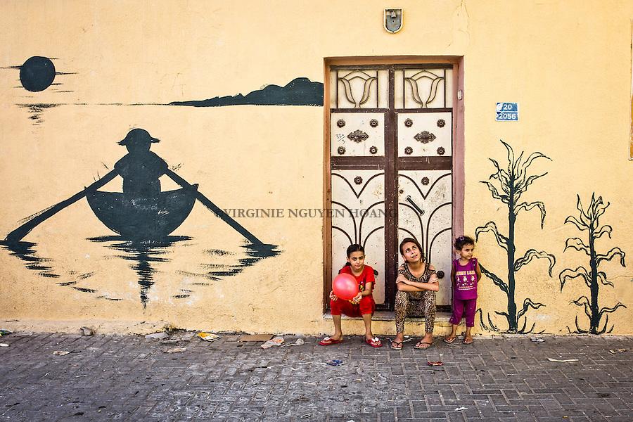 GAZA, Zaytoun: Childrens are playing in the streets of Zaytoun. Each resident of the neighbourhood has painted his wall and door in a way that it fits with the rest of the street. 14/08/15<br /> <br /> GAZA , Zaytoun : Des enfants jouent dans les rues de Zaytoun. Chaque habitant du quartier a peint son mur et sa porte d'une mani&egrave;re qui correspond avec le reste de la rue. 14/08/15