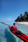 Belize, Lime Cay: Woman sea kayaker, white-sand beach, palm trees, island off Placencia, the south coast of Belize, released,.