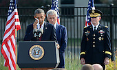 United States President Barack Obama wipes his face due to the heat and humidity as he makes his remarks at the 12th anniversary commemoration of the 9/11 terrorist attacks at the Pentagon Memorial at the Pentagon in Washington, DC on September 11, 2013. Nearly 3,000 people were killed in the attacks in New York, Washington and Shanksville, Pennsylvania. Behind him are U.S. Secretary of Defense Chuck Hagel and Chairman of of the Joint Chiefs of Staff General Martin Dempsey.   UPI/Pat Benic<br /> Credit: Pat Benic / Pool via CNP