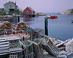 Halifax County, Nova Scota<br /> Wooden lobster traps on a dock in Peggy's Cove with morning fog enveloping the village and harbor