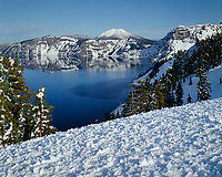 ORCL_015 - USA, Oregon, Crater Lake National Park, Evening light warms snowy rim of Crater Lake in late afternoon and distant Mount Scott.