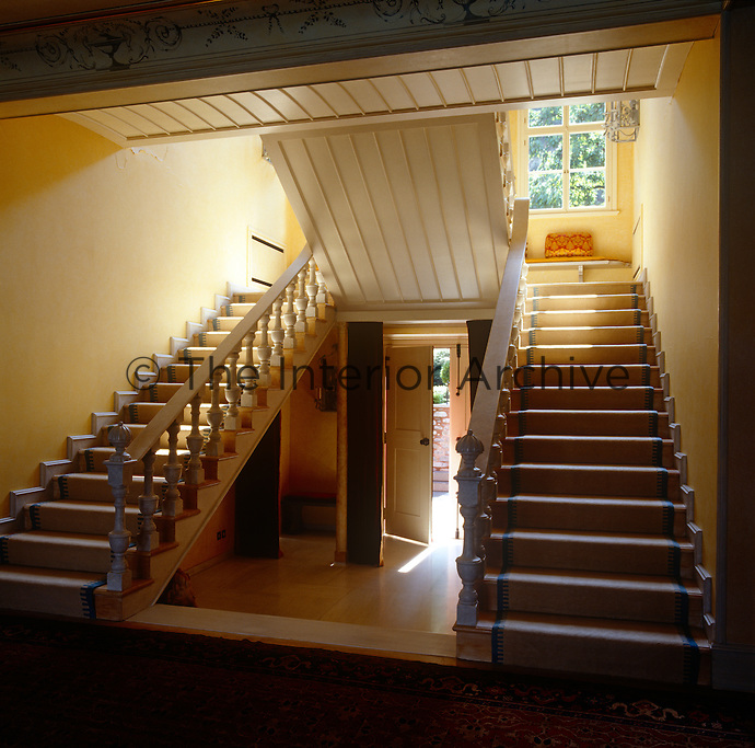 Two staircases frame the entrance door to the house, their steps leading up to a sunny window seat overlooking the garden