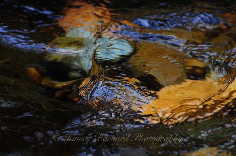 Water running over colorful creek bed rocks at Pinkham Creek Kootenai National Forest Montana