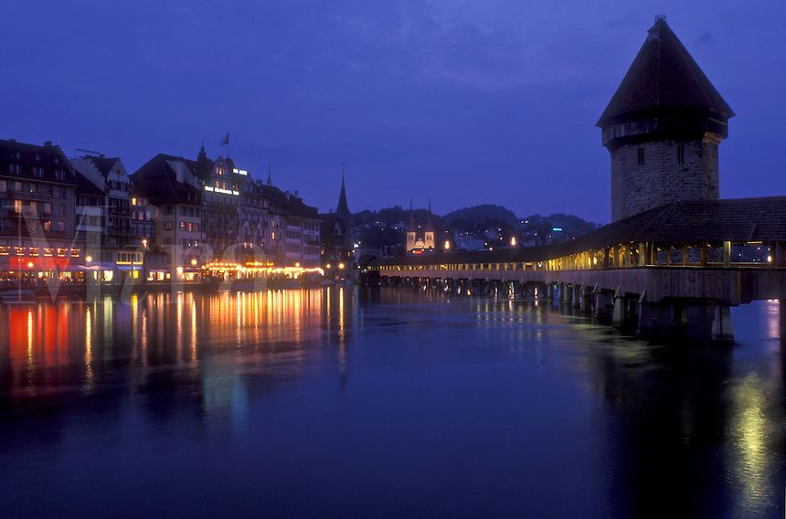 AJ1688, Lucerne, covered bridge, Switzerland, Luzern, Europe, The 14th century covered pedestrian bridge, the Kapellbrucke, on the Reuss in the evening in Lucerne is a picturesque landmark in the Canton of Lucerne. The octagonal stone tower alongside is called the Wasserturm (water tower).